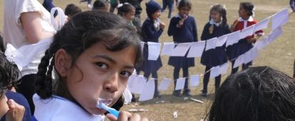 A child brushes her teeth outside a school during a hygiene workshop run by Projects Abroad Dentistry interns in Nepal.